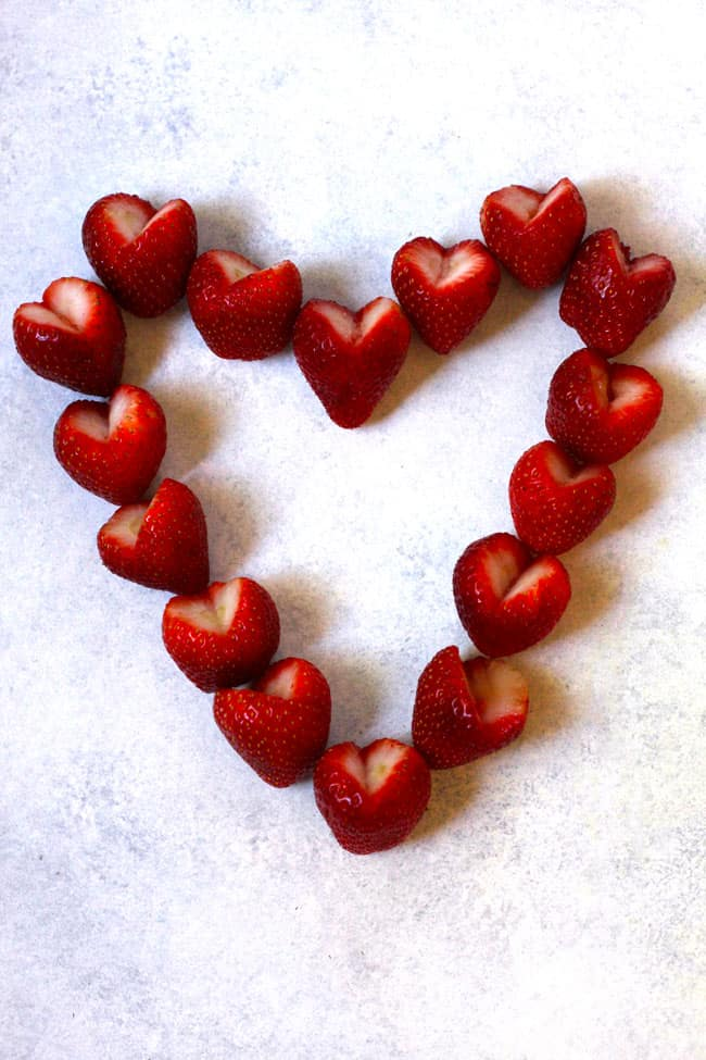 Overhead shot of strawberries cut into hearts, forming a large heart on a white background.