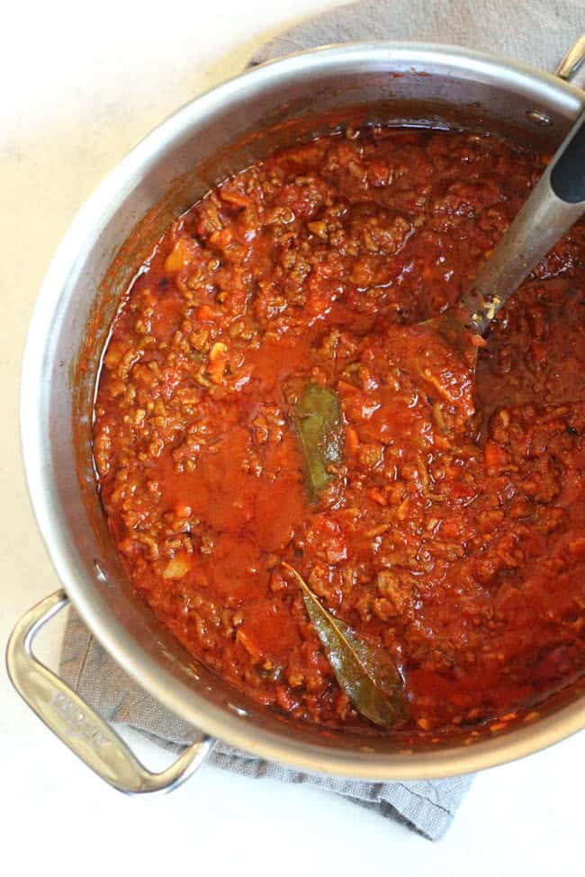 Overhead shot of a large stock pot of bolognese sauce, with a large spoon inside, with bay leaves on top.