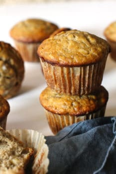 Side shot of stacked banana muffins, with a blue napkin.