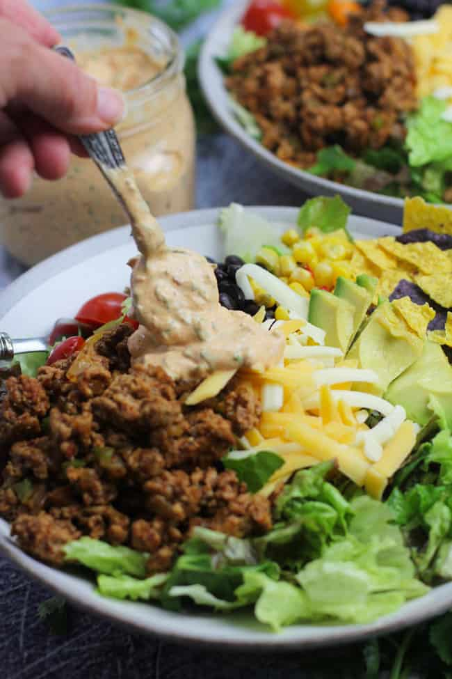 Side shot of a bowl of healthy taco salad, with a hand drizzling dressing on it.