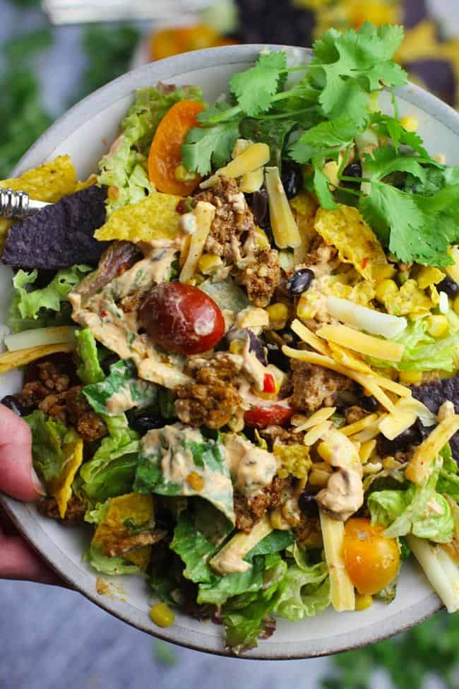 Overhead shot of my hand holding a bowl of healthy taco salad, with creamy chipotle dressing.