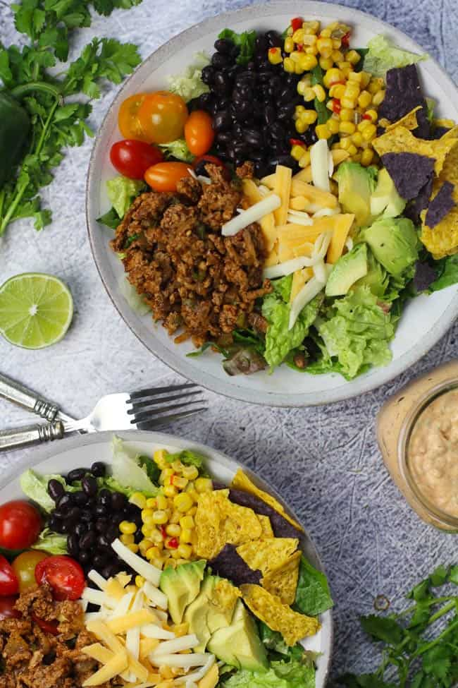 Overhead shot of two large bowls of healthy taco salad, with chipotle ranch dressing in a jar.