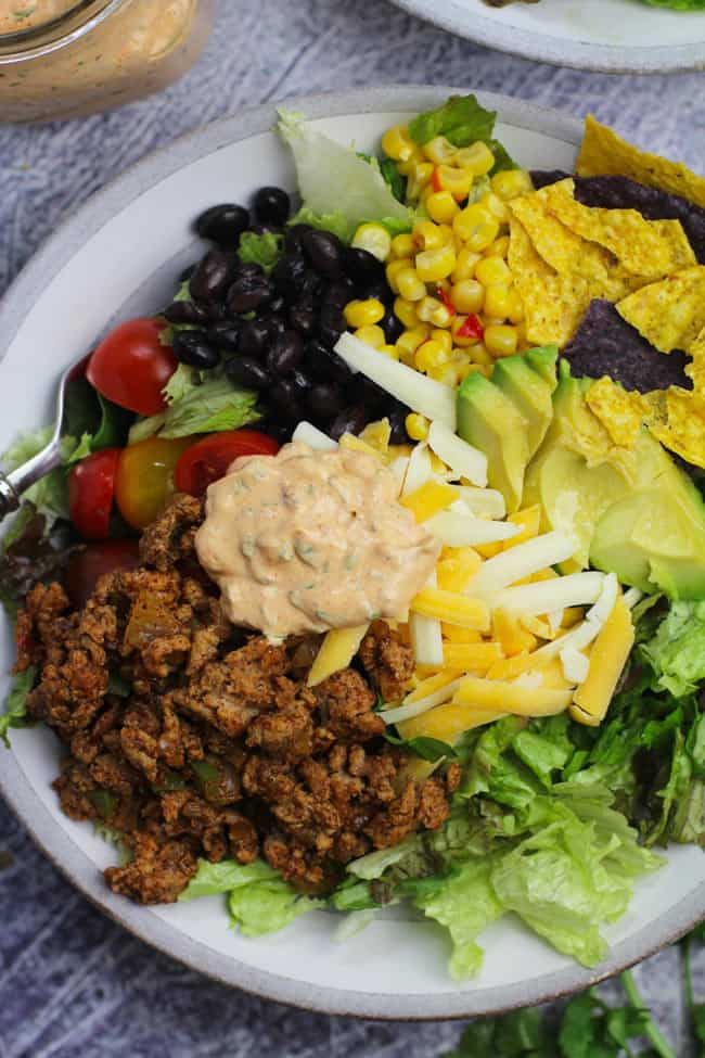 Overhead shot of a bowl of healthy taco salad, separated by ingredient.
