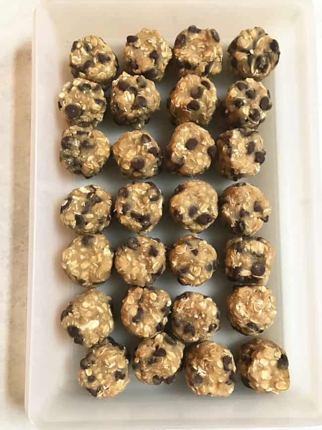Overhead shot of 28 balls of oatmeal chocolate chip cookie dough balls in a clear container.