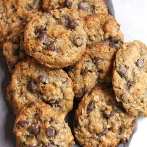 Overhead shot of oatmeal chocolate chip cookies in a pile, on a gray napkin.