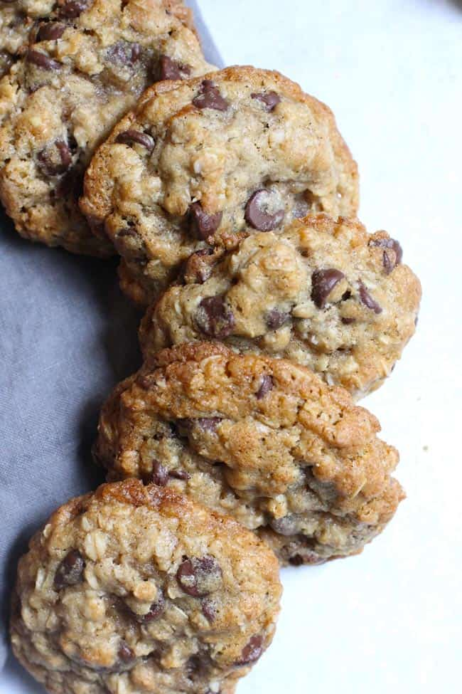 Overhead shot of a stacked curve row of oatmeal chocolate chip cookies, on a gray napkin.