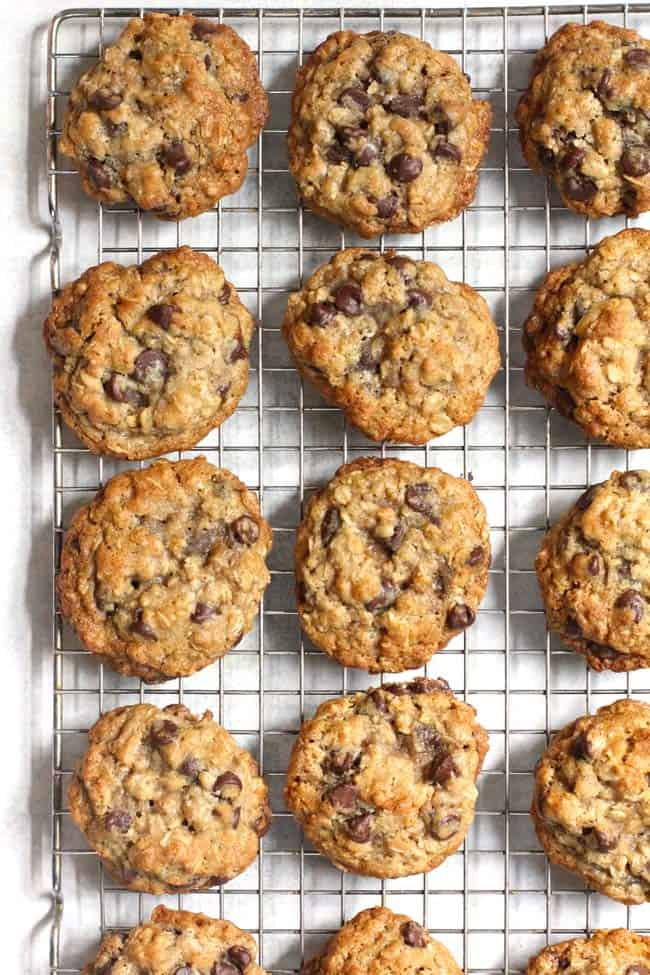Overhead shot of oatmeal chocolate chips laid out on a cooling rack, on a white background.
