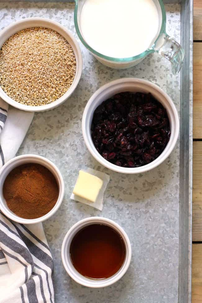 Overhead shot of steel cut oat ingredients in separate bowls, on a gray tray.