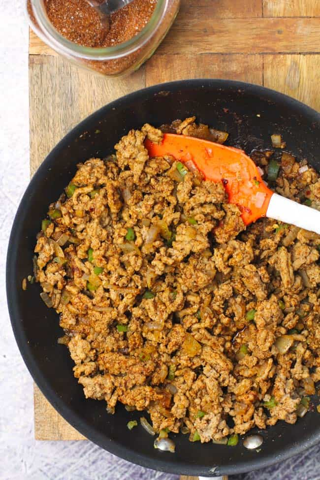 A skillet of taco meat, with a spatula, on a wooden board.