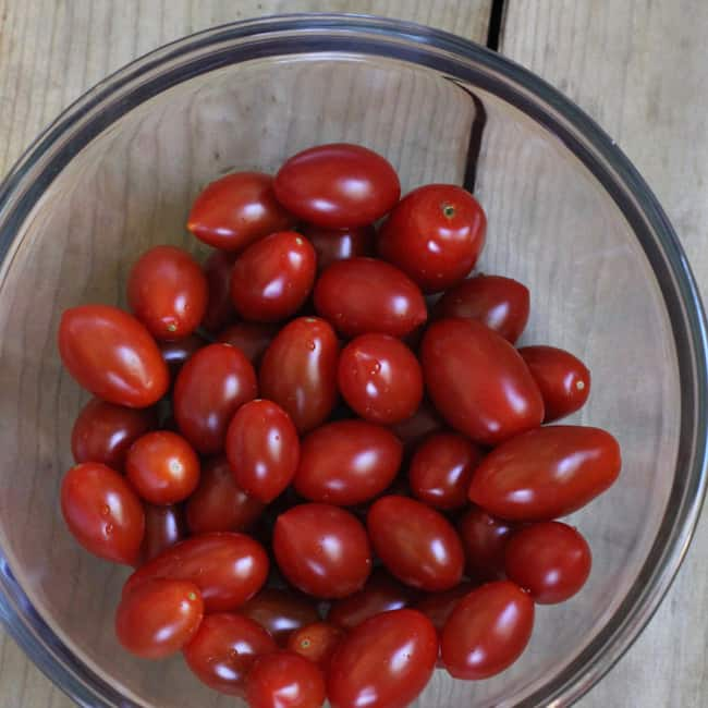A bowl of cherry tomatoes in a glass bowl.