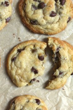 Overhead close-up shot of chocolate chip cookies, one broken apart, on tan parchment paper.