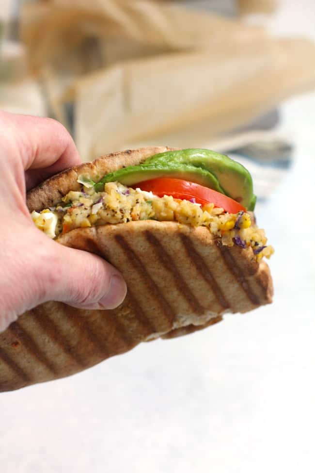 Close up shot of my hand holding a chickpea salad sandwich.