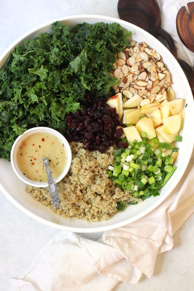 Overhead shot of kale and quinoa salad in a large white bowl, separated by ingredient, with a small bowl of dressing.