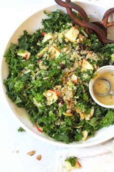 Overhead shot of large white bowl of kale and quinoa salad, with wooden salad tongs, and small bowl of Honey Dijon dressing.