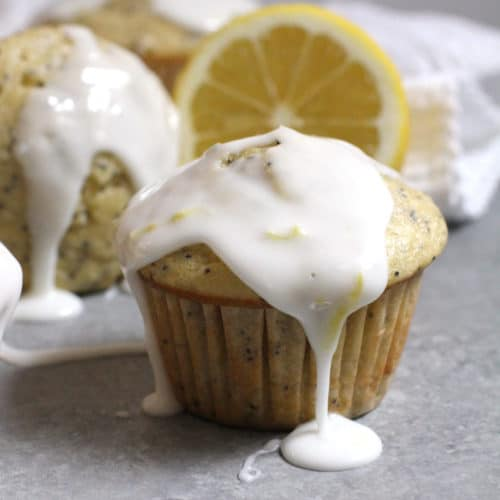 Side shot of glazed poppy lemon poppy seed muffins, with glaze dripping off, on a gray background with white napkin.