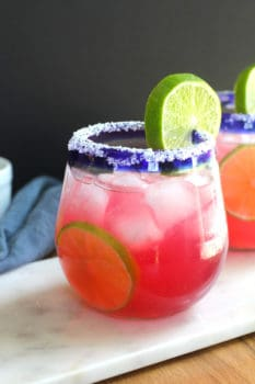 Side shot of a cranberry margarita, in a blue rimmed glass, with a salt rim and lime wedge, on a white board.
