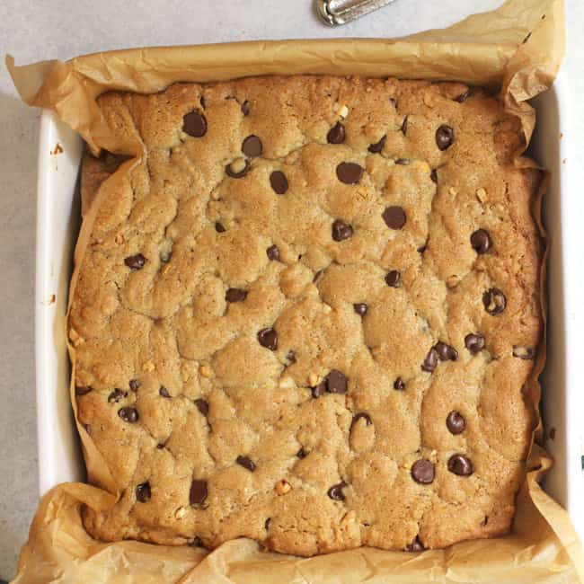 Overhead shot of a dish of chocolate chip peanut butter blondies, with parchment paper.