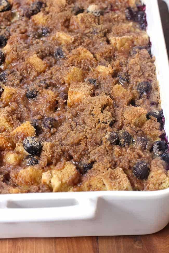 Side shot of a 9x13 white casserole dish of blueberry French toast.