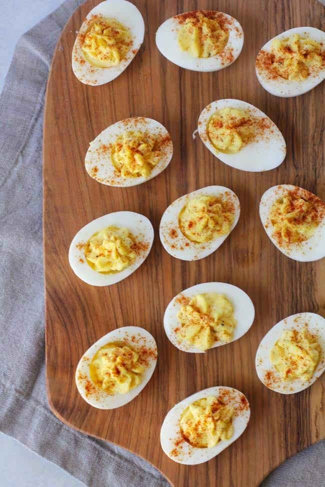 Overhead shot of deviled eggs on a wooden board.