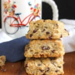 Side shot of three stacked crumbly chocolate chip scones, on a wooden background with a white bicycle mug in the background.