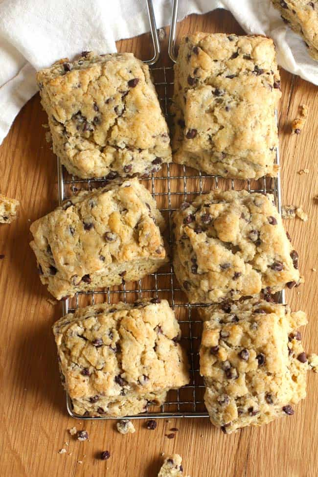 Overhead shot of six crumbly chocolate chip scones on a wire rack, on a wooden background.