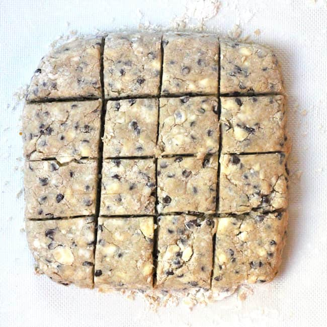 Overhead shot of the scone dough, cut into 16 squares on a white flour background.