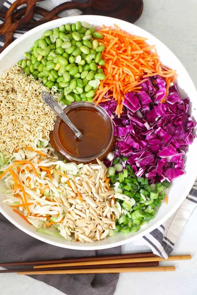 Overhead shot of Crunchy Asian Cabbage Salad in a white bowl, separated by ingredient, with salad dressing in the center.