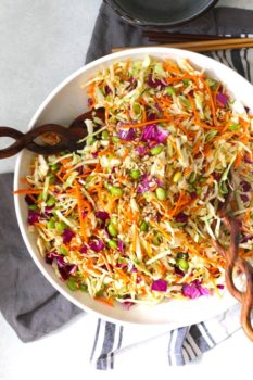 Overhead shot of Crunchy Asian Cabbage Salad in a white bowl with brown salad tongs.