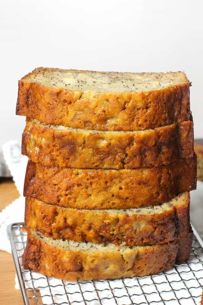 Side shot of a stack of banana bread slices, on a wire rack, with a white napkin.