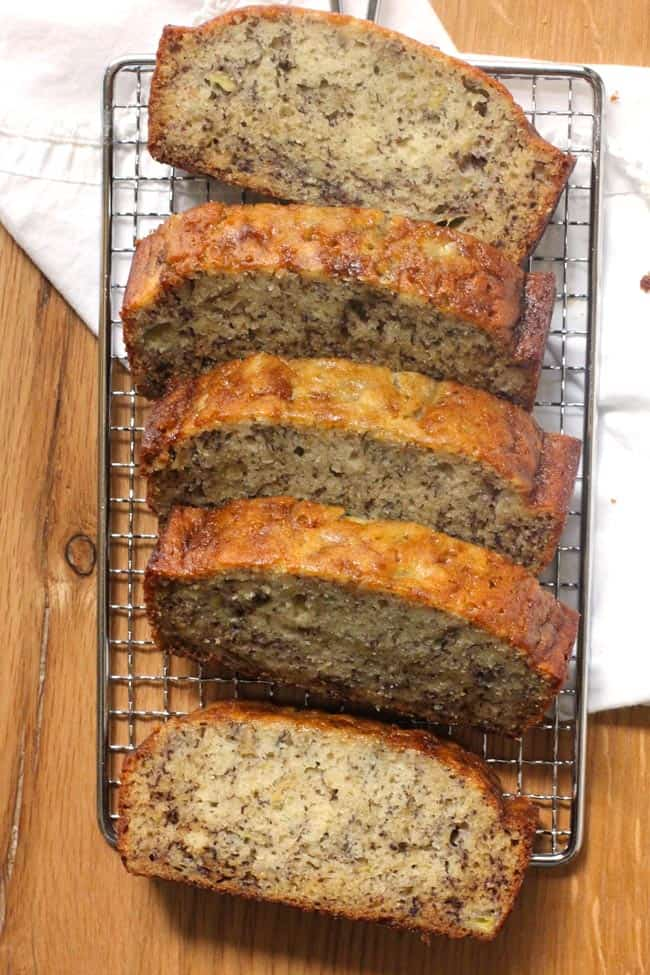Overhead shot of slices of easy banana bread on a wire rack, with a white napkin.