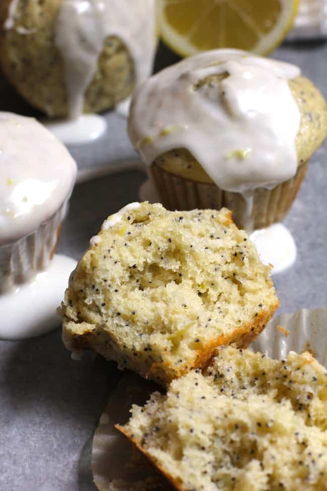 Overhead shot of lemon poppy seed muffins, one of them broken in half to see the inside.