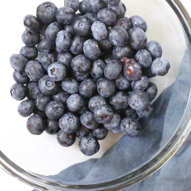 Overhead shot of fresh blueberries in a clear bowl, with a blue napkin.