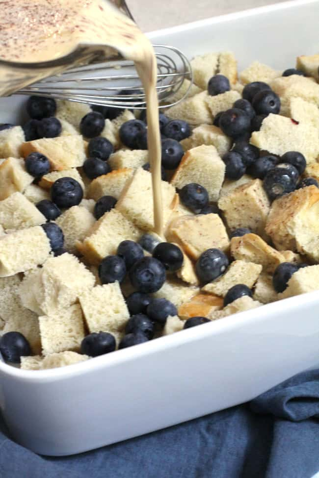 Side shot of egg custard being poured over the cubed bread and blueberries, in a white casserole dish.