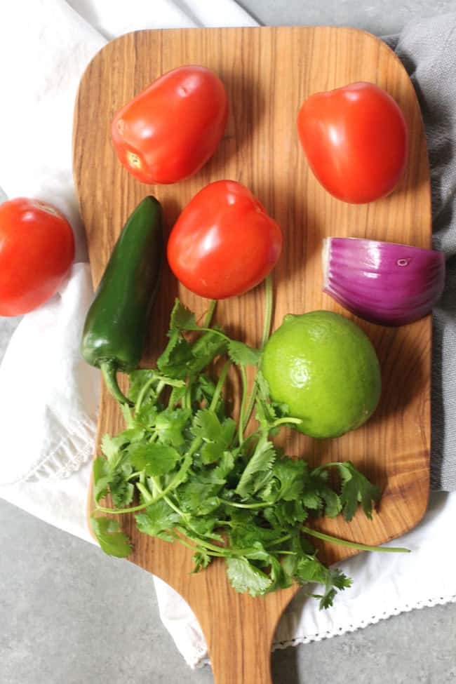 Overhead shot of Pico de Gallo ingredients: Roma tomatoes, jalapeño, red onion, cilantro, and lime.