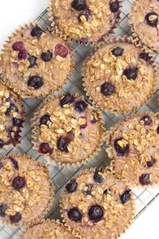 Overhead shot of Blueberry Baked Oatmeal Cups in jumbo liners, on a wire cooling rack.