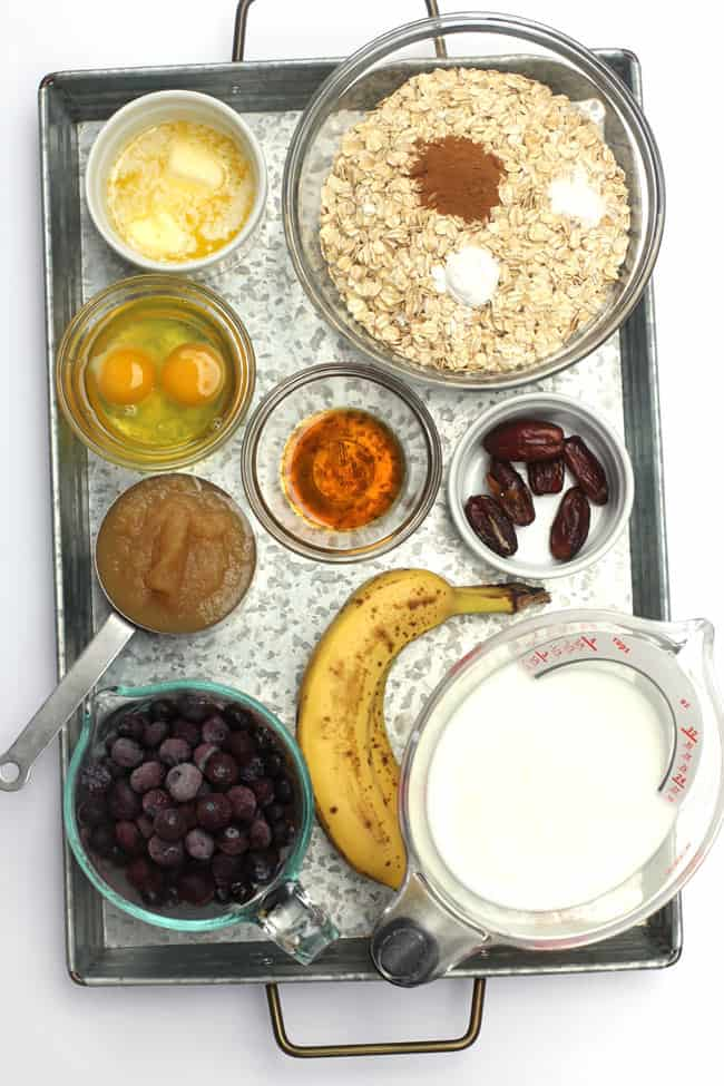 Overhead shot of all the ingredients for Blueberry Baked Oatmeal Cups, on a gray tray.