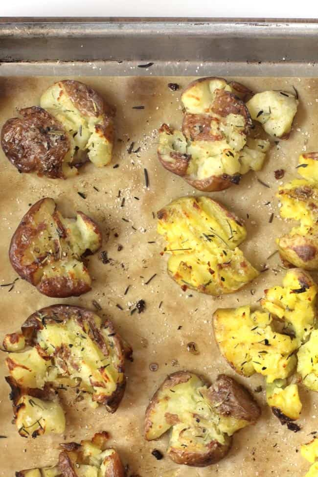 Overhead shot of a corner of a sheet pan of Herb Butter Smashed Potatoes, on tan parchment paper.
