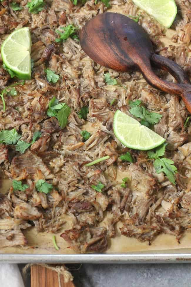 Overhead shot of the crispy pork on a sheet pan, with limes and cilantro.