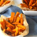 Overhead shot of Spicy Baked Sweet Potato Fries in white bowls, on a blue napkin.
