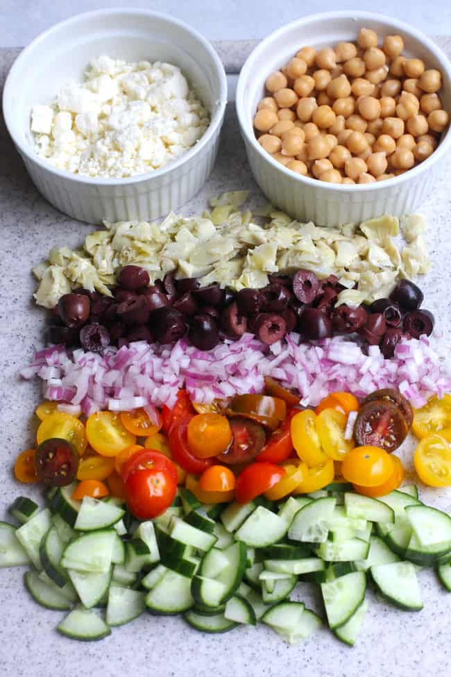 Overhead shot of the chopped ingredients in the pasta salad, lined up, with bowls of feta cheese and chickpeas.