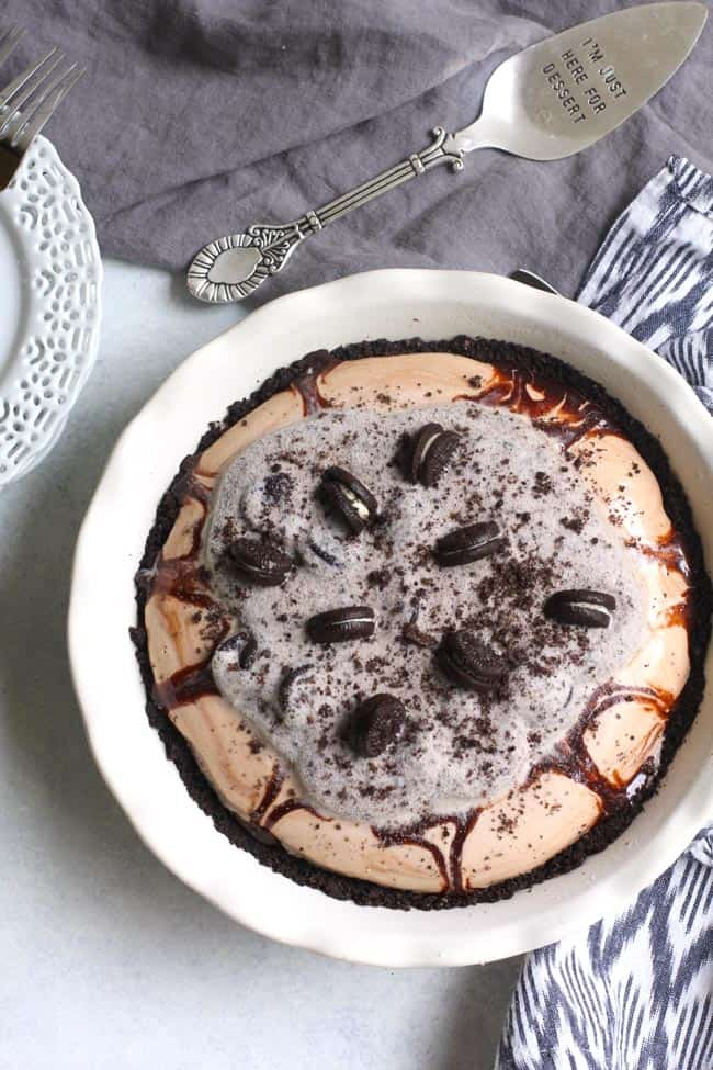 Overhead shot of Oreo Ice Cream Pie in a white pie dish, with gray and white napkins.