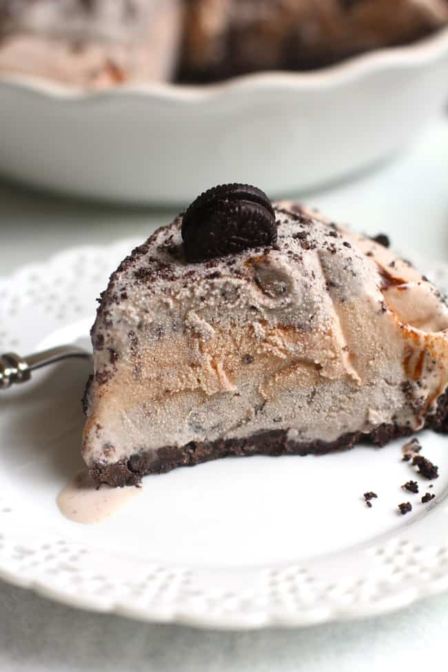 Side shot of one slice of Oreo ice cream pie on a white plate, with the remaining pie in the background.