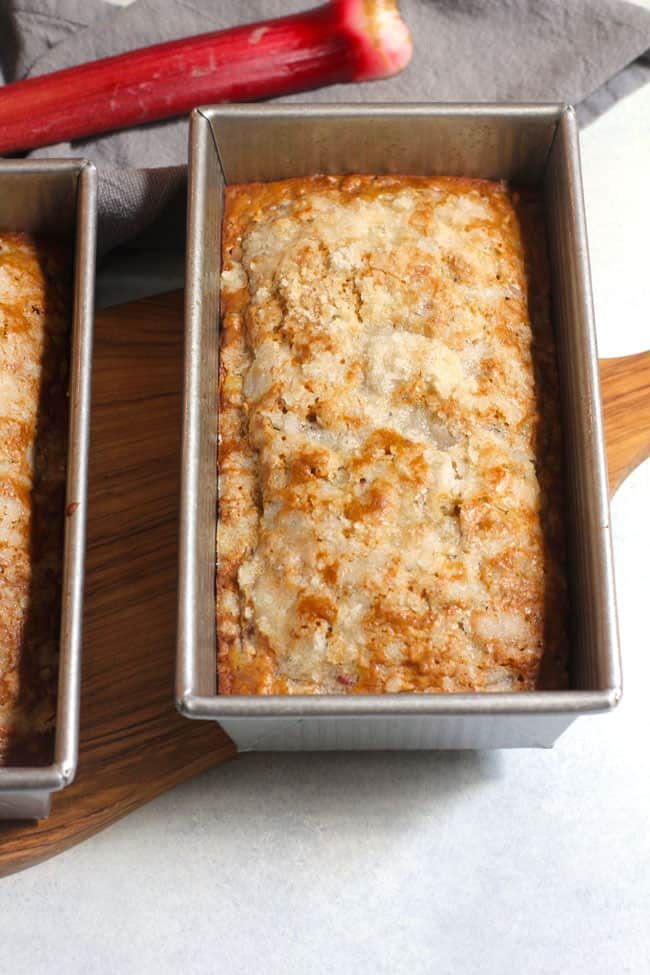 Side shot of a pan of rhubarb nut bread, on a white background.