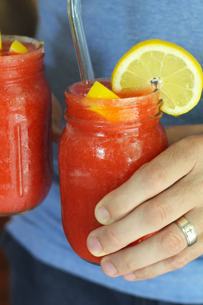 Side shot of hands holding two mason jars of strawberry lemonade vodka slushies.