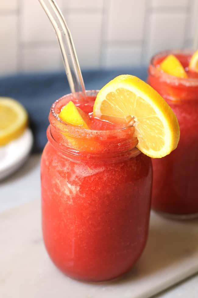 Side shot of two mason jars of strawberry lemonade vodka slushies, with lemon slices and glass straws.