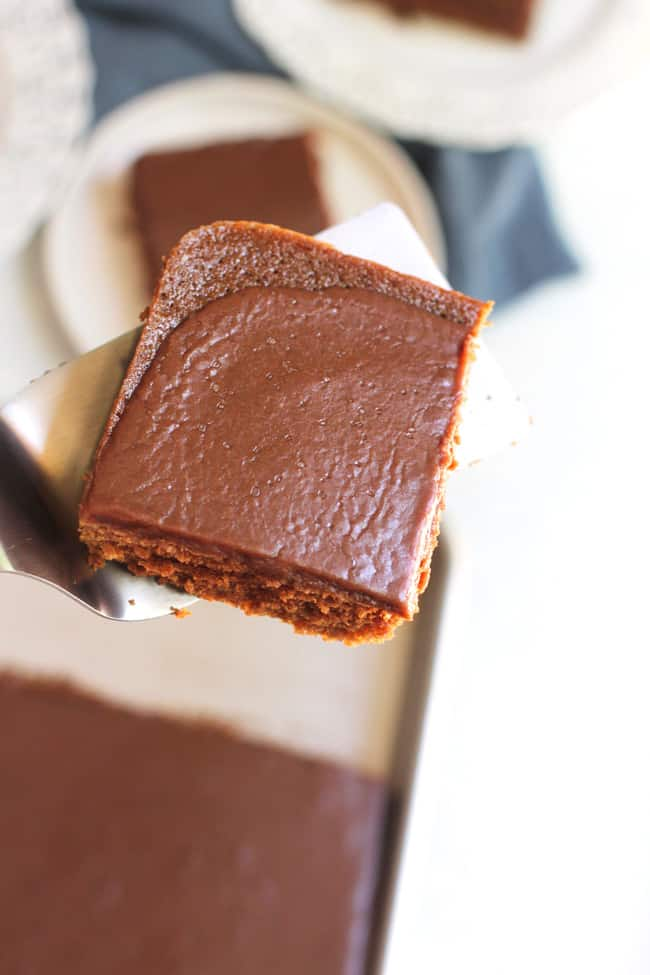 A close up of one brownie on a spatula, with the pan of brownies in the background.
