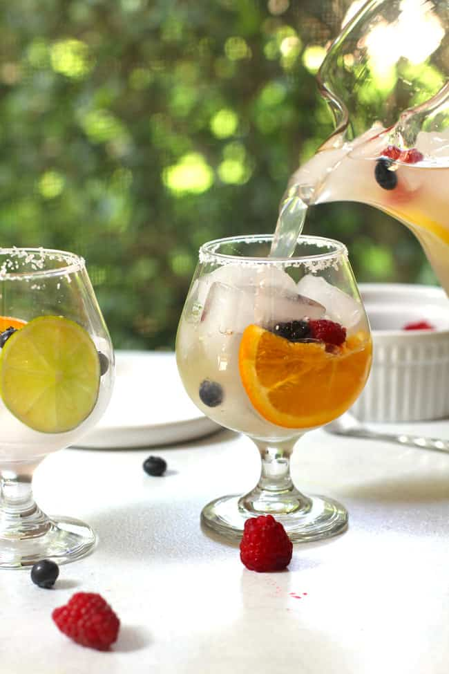 A pitcher of tequila sangria being poured into a glass decorated with fresh fruit, with greenery in the background.