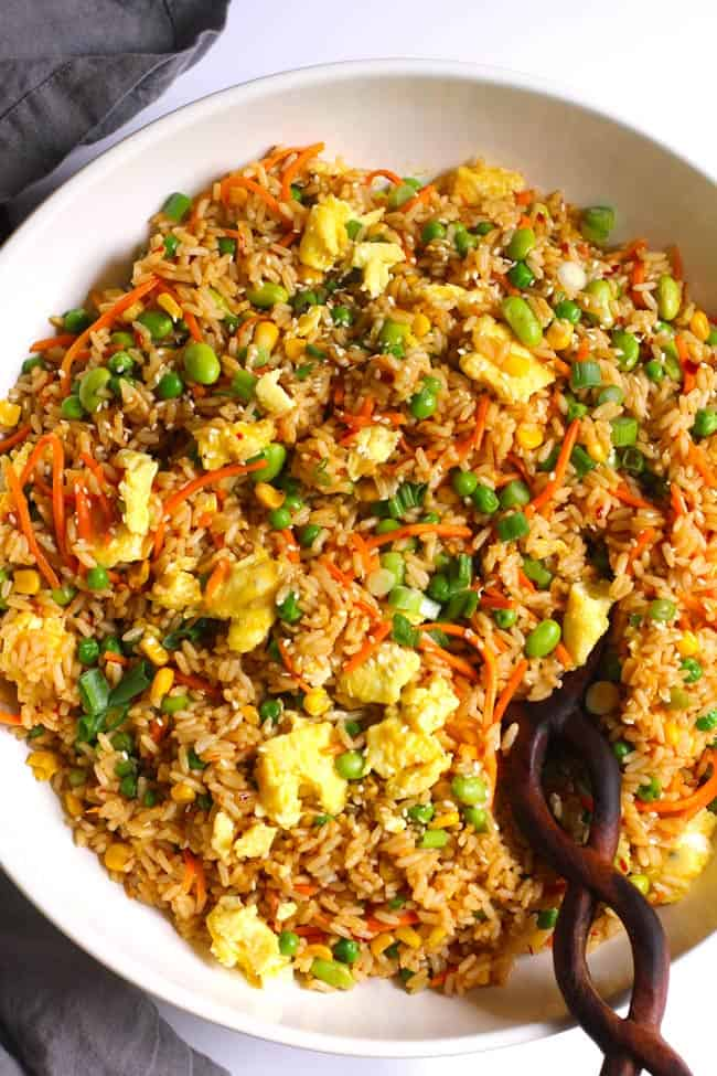 Overhead shot of a large white bowl of spicy fried rice, with a wooden spoon on a white background.