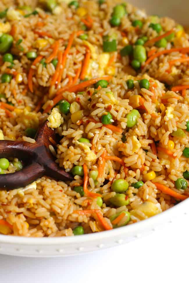 Close-up shot of a large white bowl of spicy fried rice, with a wooden spoon on a white background.