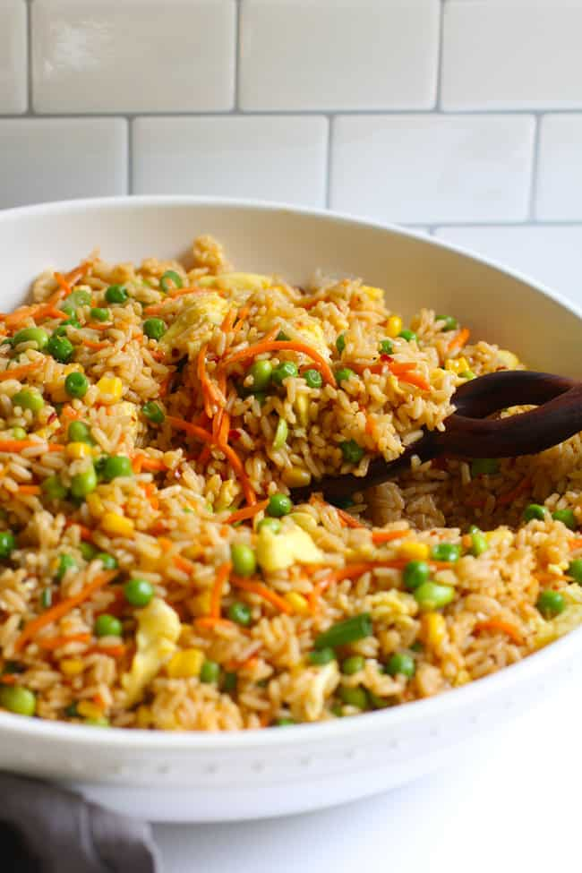 Side shot of a large white bowl of spicy fried rice, with a wooden spoon on a white background.